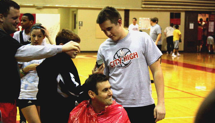 Shaving the head.  Bacon gets his head shaved by Powell-Littler in celebration of the team's first victory.