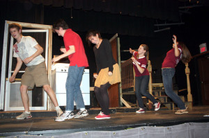Students mime fighting strong wind.