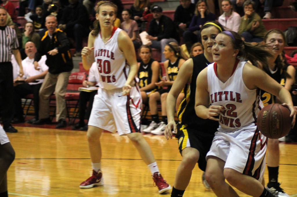 Mickey Hansche drives against Bettendorf as Harper Beasley looks on.  Photo by Annika Wasson