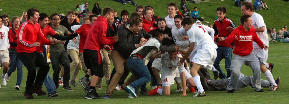 Scott Tribbey 14 falls to the ground amidst the rush of City High fans after City defeated West on a last second goal.