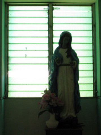 A Guadalupe statue sits in front of a green tinted window of a church.