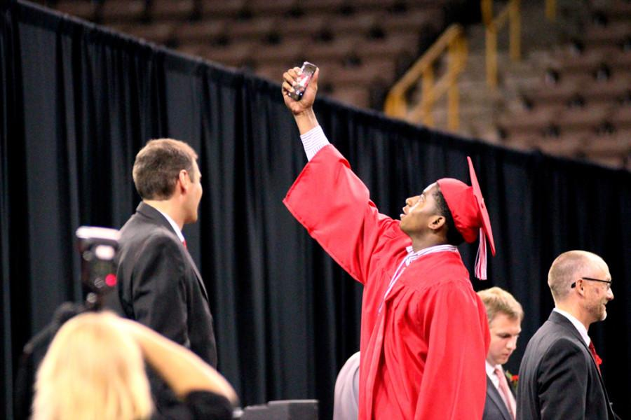 Jamarty Hall 14 takes a selfie while walking across the stage at graduation.
