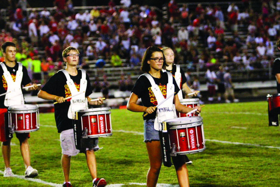The drum line performs during halftime at a home football game.