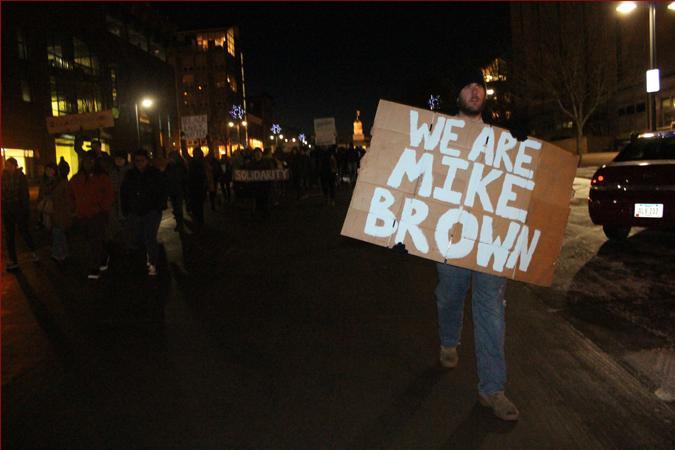 A protestor walks down Iowa Ave.