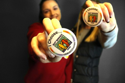 Seniors Payton Evans and Lillie Christopherson show their support buttons for the Spread the Word to End the Word Campaign.