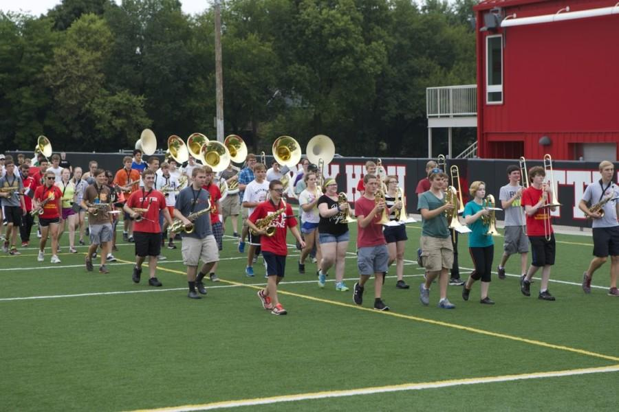 Marching band students practice on the soccer turf.