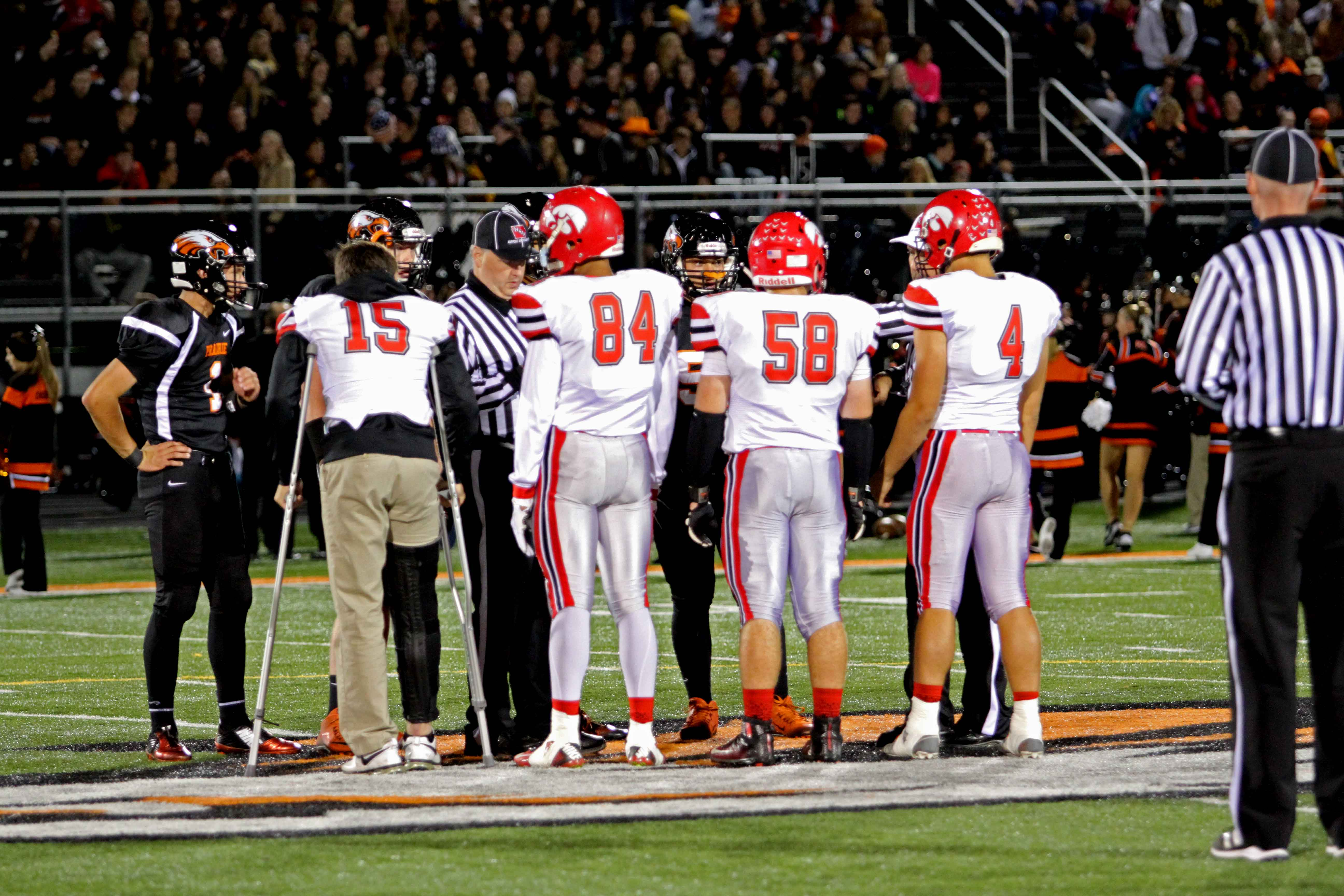 Nate Wieland '17 joins his fellow captains on the field for the coin toss on crutches following his injury early in the previous weeks game versus Ottumwa.
