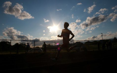 A City High runner runs through the first turn while being silhouetted by the sun on Thursday, May 12th, 2016.