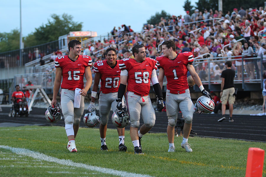 Nate Wieland '17 (#15), Naeem Smith '17 (#20), Joey Schnoebelen '17 (#58), and Brock Hunger '17 (#1) chat on the sidelines before the game.
