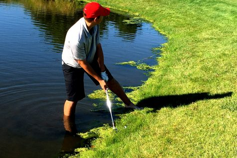 A City High golfer hits the ball from the water during the district meet.