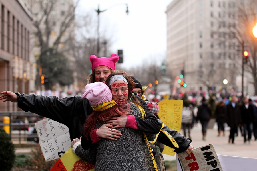 Friends reunite at the peaceful protest while wearing the popular pussy hats.