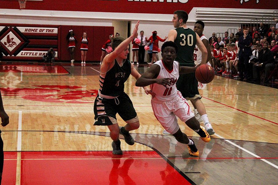 Kolbie Barnes '17 drives to the basket while being guarded by West High's Evan Flitz '18.