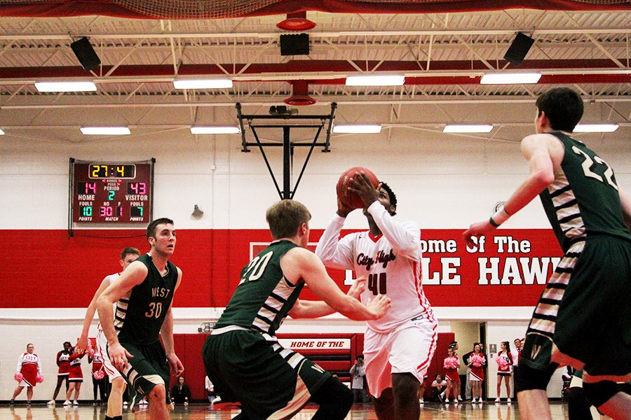 Chuck Johnson '17 goes up for a shot against West High's Nate Disterhoft '17 in the first half against the Trojans.