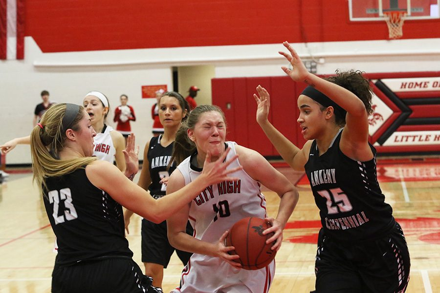 Ashley Joens '18 drives to the basket while being guarded by Ankeny Centennial's KeAnna Williams (#25) '18 and Kenna Sauer '19 (#23).