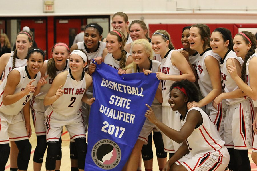 The+City+High+girls+basketball+team+poses+with+the+state+qualification+banner+after+defeating+the+Ankeny+Centennial+Jaguars+48-32.+