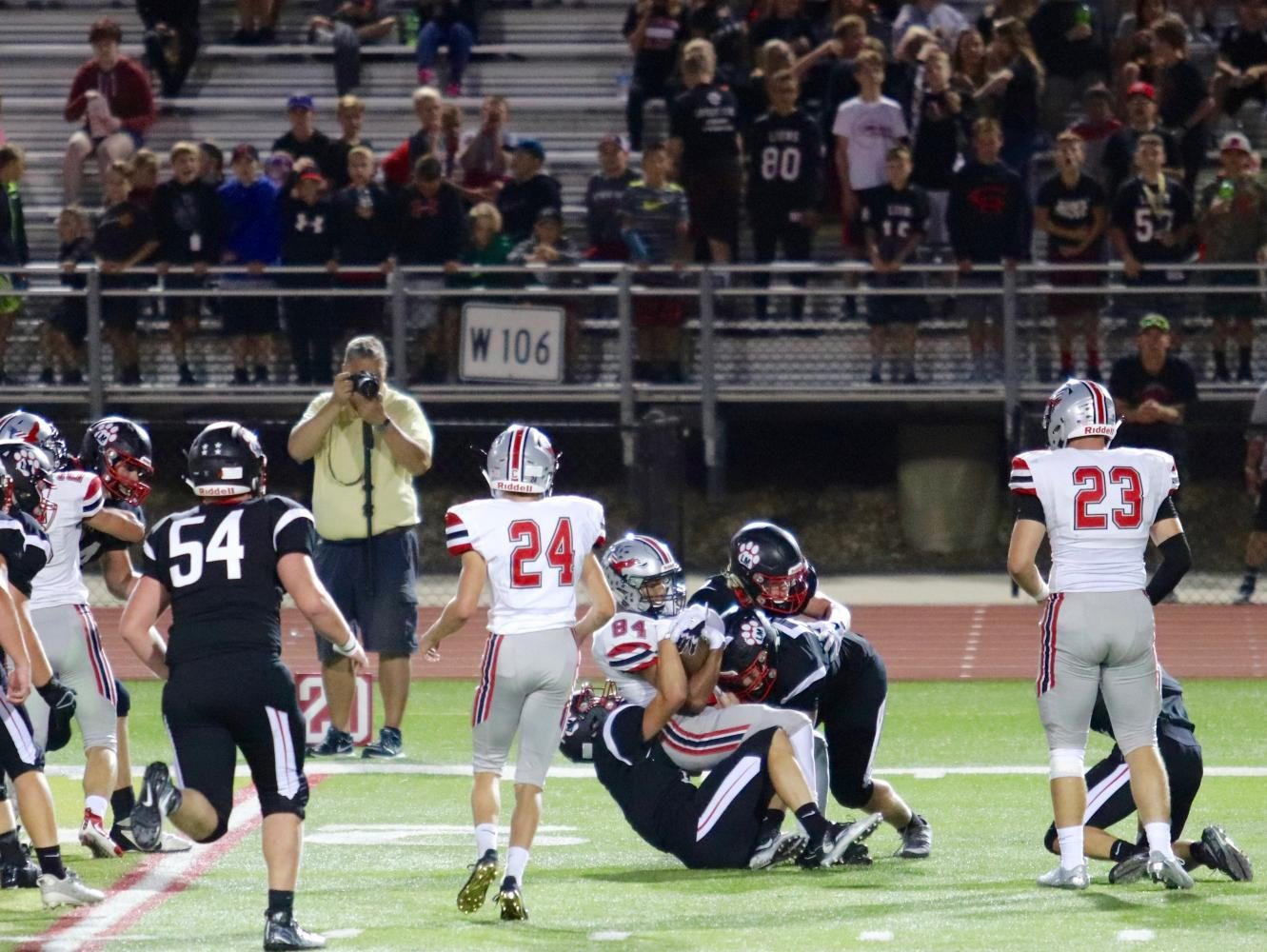 Zach Jones 18 holds on to the ball as three Linn-Mar players tackle him.