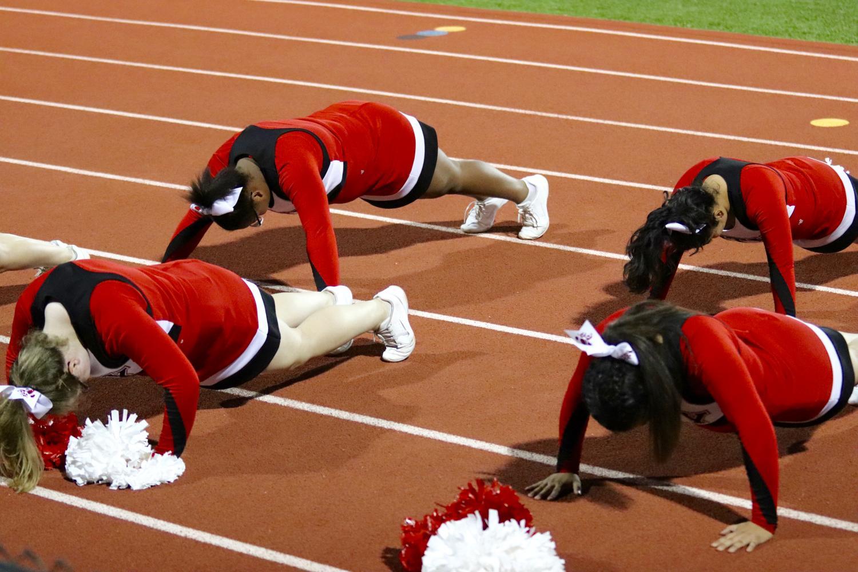Little Hawk Cheerleaders pump out 20 push-ups, to match the score, Friday night at Linn-Mar stadium