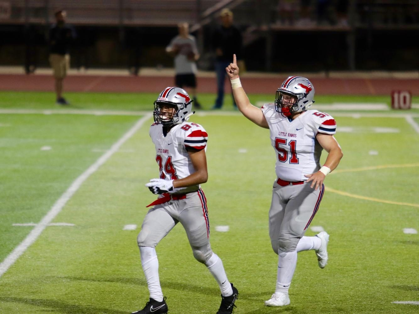 Teammates Liam McComas 19 (51) and Zach Jones 18 (84) celebrate after Jones second touchdown of the night.