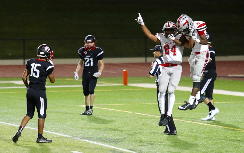 Teammates Zach Jones 18 (84) and Malik Kimber 19 (5) celebrate after Jones touchdown Friday night at Linn Mar Stadium.