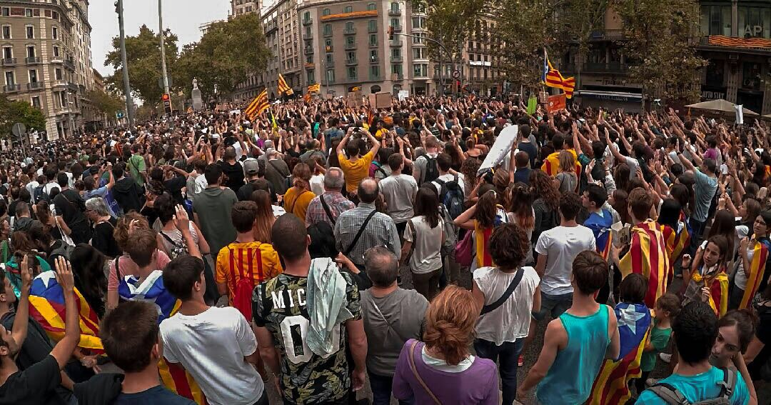 Catalan citizens raising their hands up as a sign of peace during a protest.