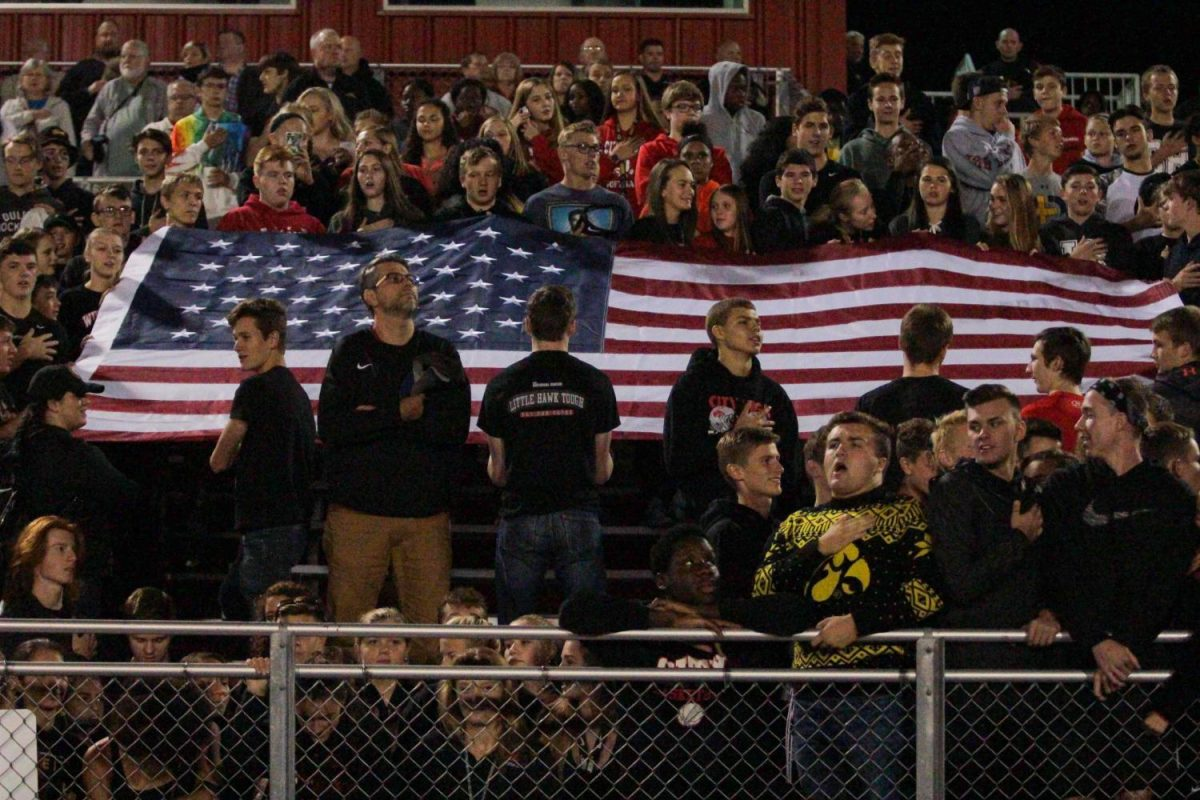 At the varsity football game student protestors knelt while counter-protestors held a flag behind them.  Assistant Principal Scott Jespersen stands in between the protests.