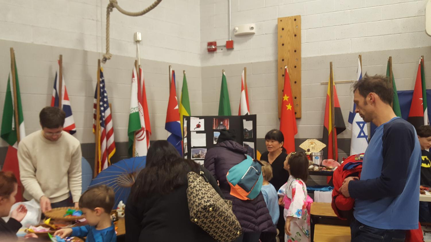 Elementary students and parents visit a country's booth.