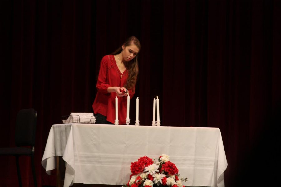 A student lights a candle during the induction ceremony.