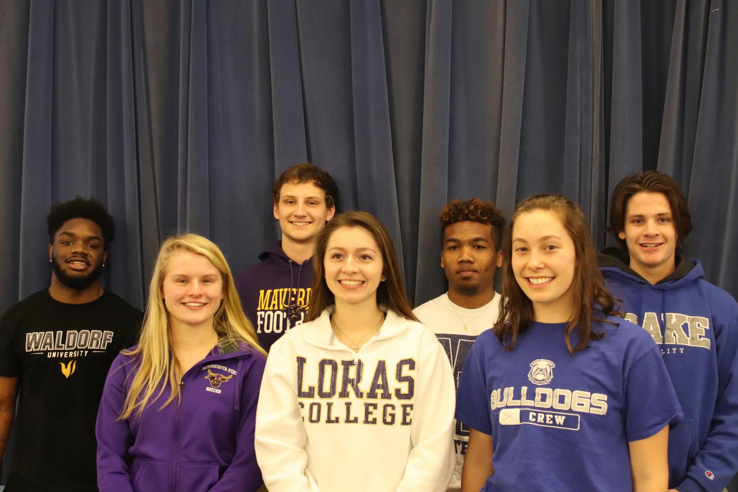 (L-R): Athletes Davonte Foster, Sydney DePrenger, Bryce Hunger, Christina Hora, Marquel Poole, Clara Froeschner, and Jackson Meyer signed the National Letter of Intent in the Cafeteria on February 7th, 2018.
