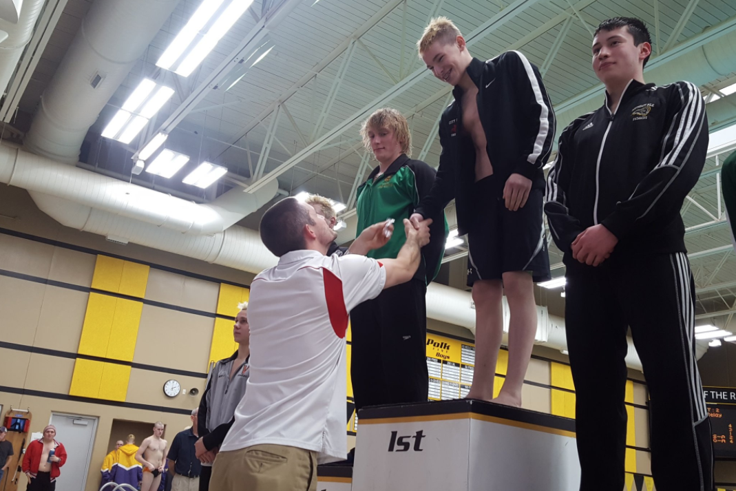 Isaac Weigel '21 receives the gold medal for his 500-yard freestyle race at the districts meet.