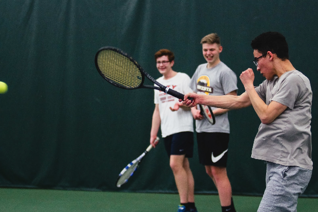 Miles Pei '18 strikes the ball in practice as Kahleb Fallon '19 and Jack Motto '19 look on.