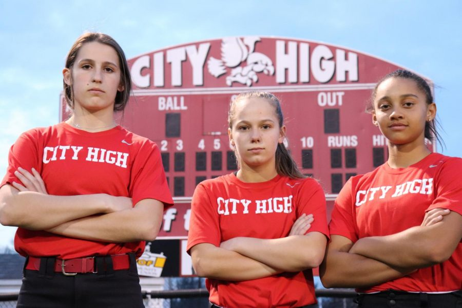 Ella Cook '21, Carey Koenig '21, and Ayana Lindsey '21 pose for a shot in front of their beloved field's scoreboard after a spring scrimmage against Liberty High School.