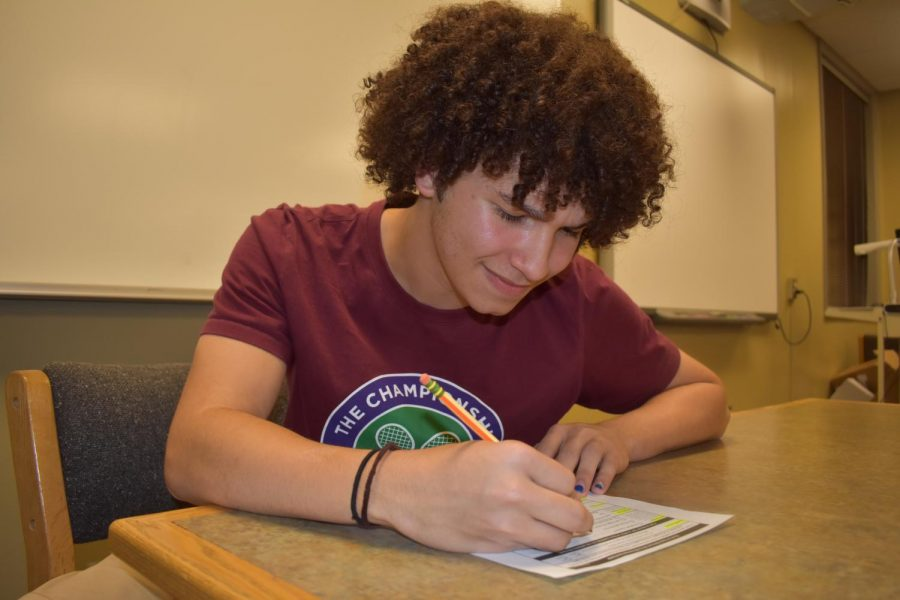 TJ Murphy '19 fills out a voter registration form. Photo by Olivia Lusala