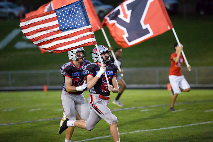 Max DePrenger '19 runs with the American Flag while the rest of the varsity team follows behind him onto the field.