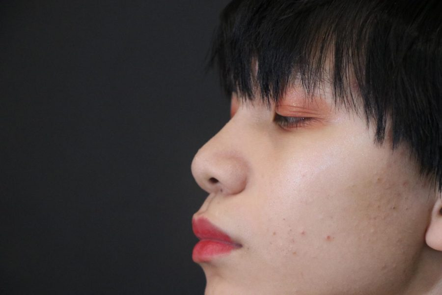 Phong Nguyen 20 poses with a bold red lip.