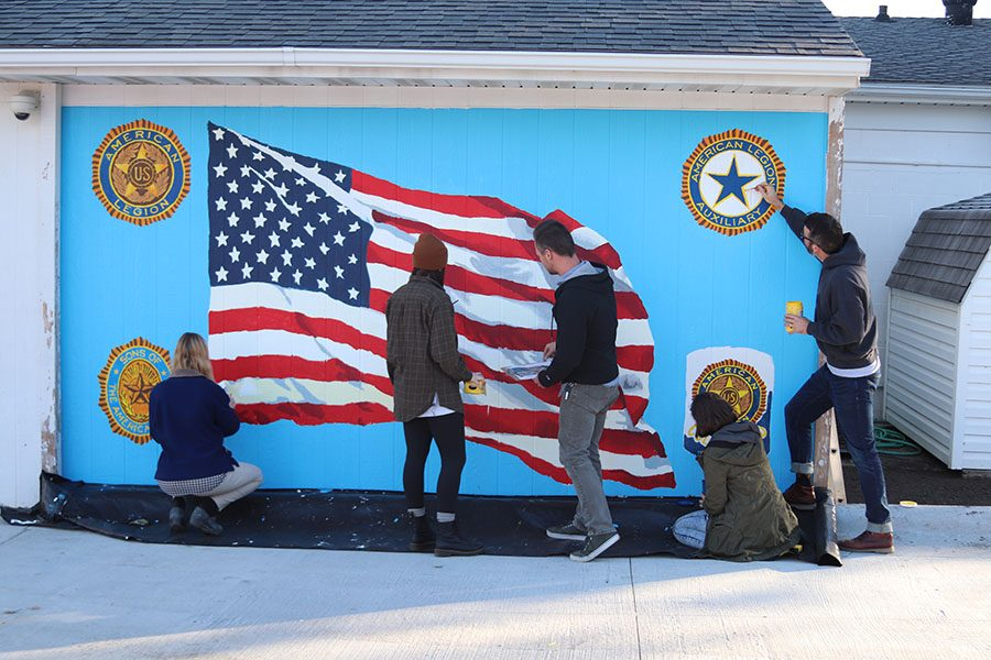 The teachers from the Art Department and two students work on painting the mural.