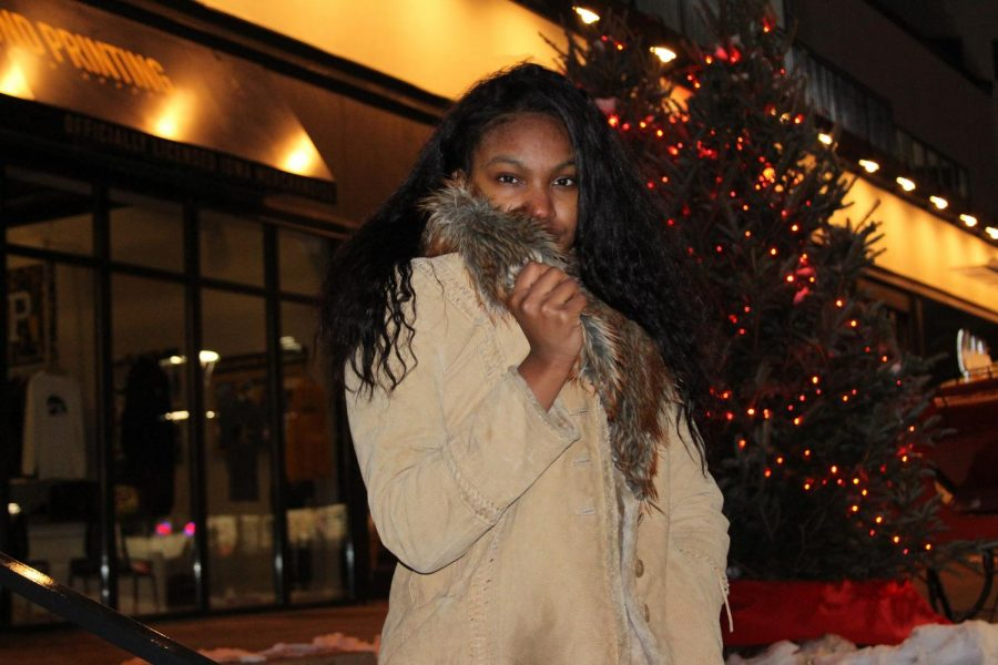 Jazsmine Vanpelt '20 shields her face from the cold with the fur trim on her coat.