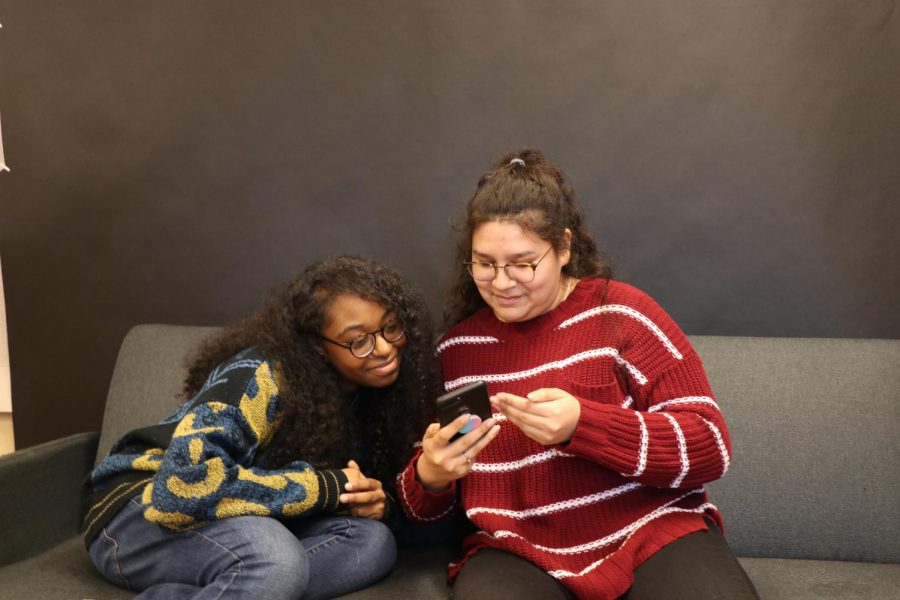 Feda Elbadri '21 (left) and Frida Escorcia '21 (right), laughing at pictures on Frida's phone.
