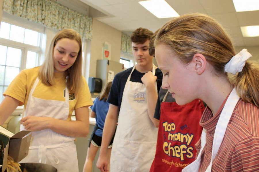Annika Rutt '22 pours pasta into pan with Jake Roth '22 and Sophia Wagner '22