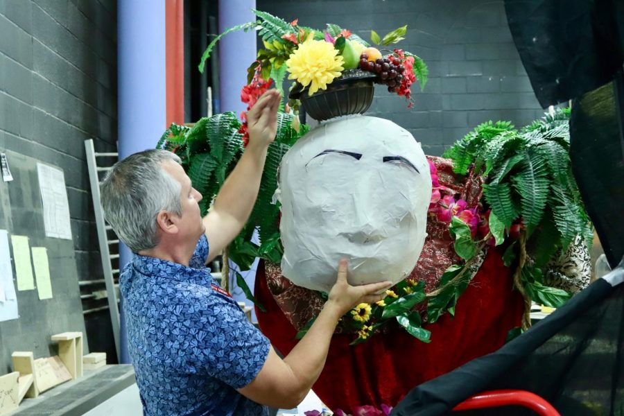 Troy Peters arranges the head of a puppet.