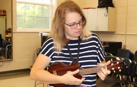 Mrs. Fields-Moffit strums her ukulele in her classroom.
