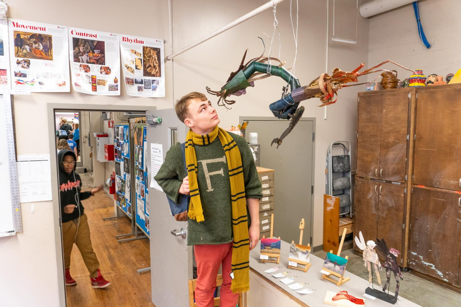 Finnegan Shelton '20 stands next to his dragon sculpture.