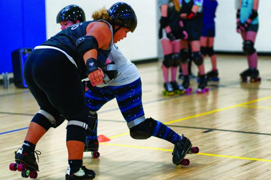Molly Hippert '21 takes on Phoebe Burt, a junior at West High, in a Iowa City Bruisers practice.