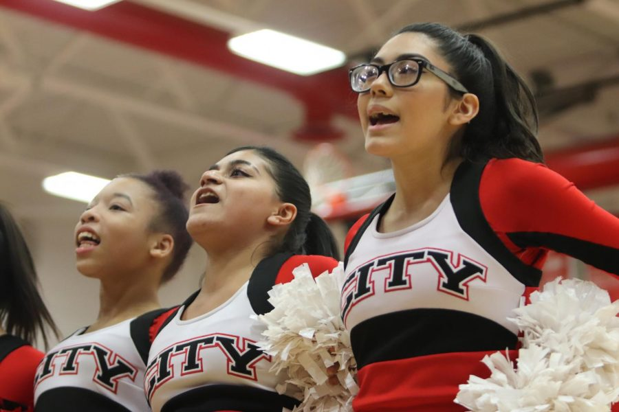 City High  cheerleaders cheering during a girls basketball game.