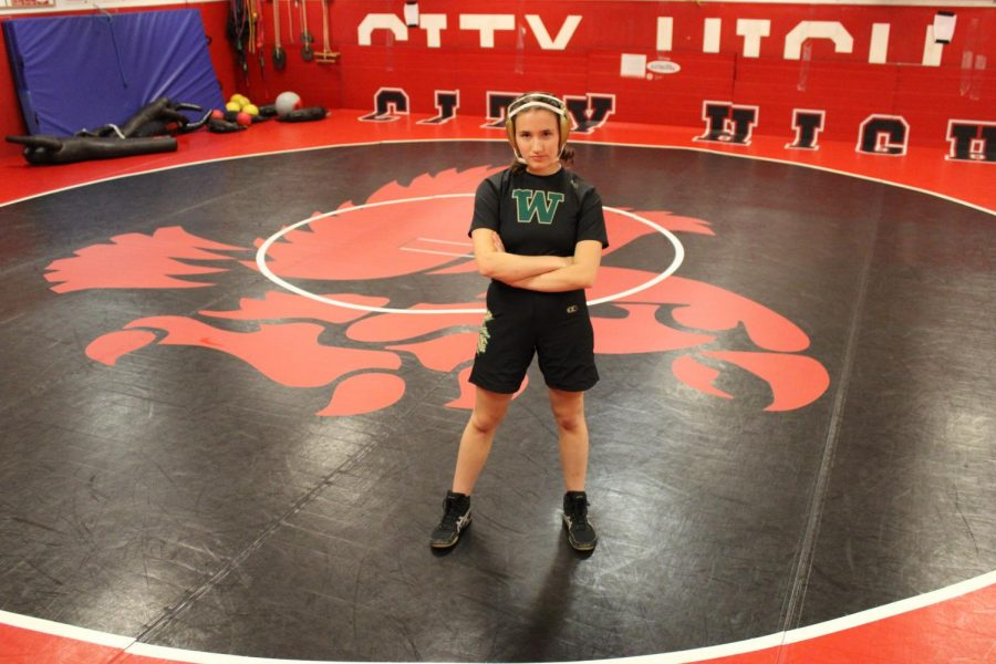 Sophia Strathearn '21 posing in the City High wrestling room with her West High girls wrestling uniform.