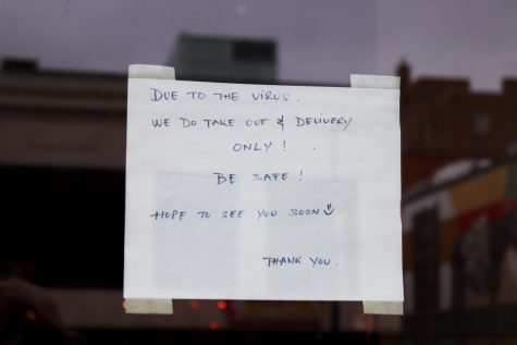 A downtown store front posts a sign of closure because of COVID-19.