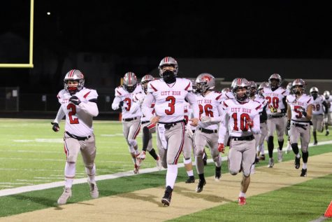 The City High football team runs onto the field before their game against West High on Friday night.