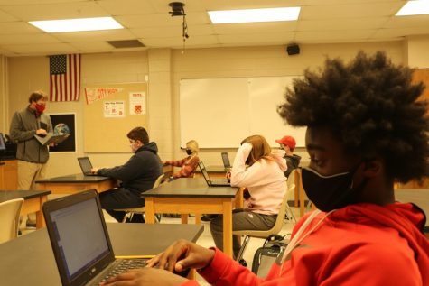 Hybrid students in class wearing masks and sitting socially distanced.