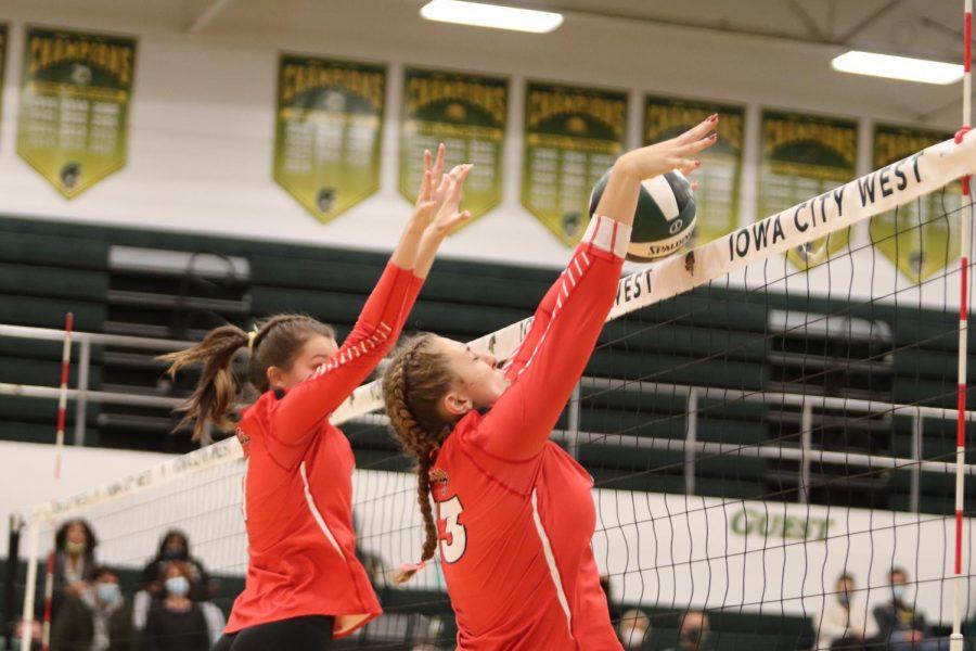 Sara Cassady '21 and Joslyn Becker '21 jump up to block the ball.