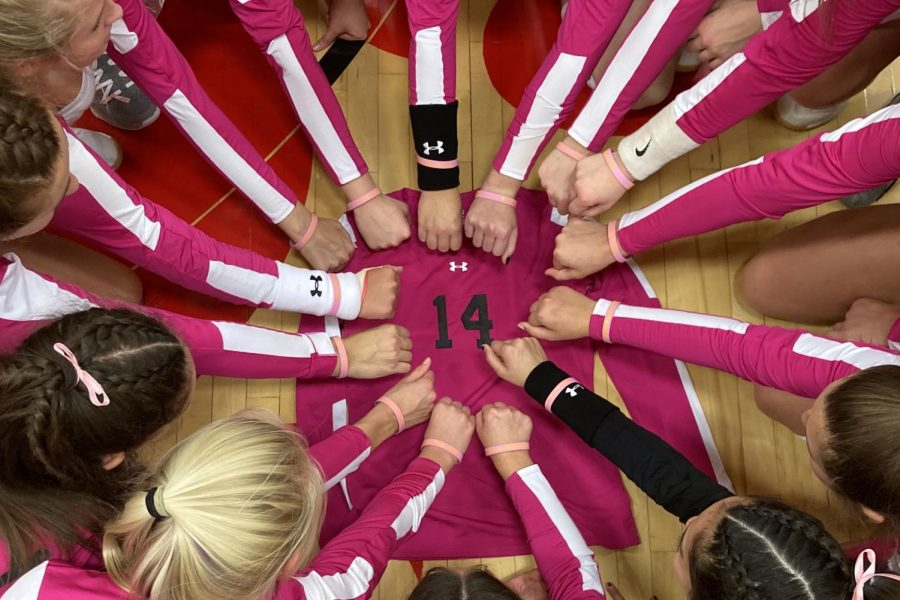 The City High volleyball team holds their hands in a circle over teammate Emma Nugents jersey. Joslyn Becker 21 had bracelets made with Emma Nugent and We play for 14 on them, which she gave to her teammates.