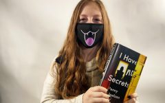 Kate Kueter '21 poses with the book I Have No Secrets by Penny Joelson.